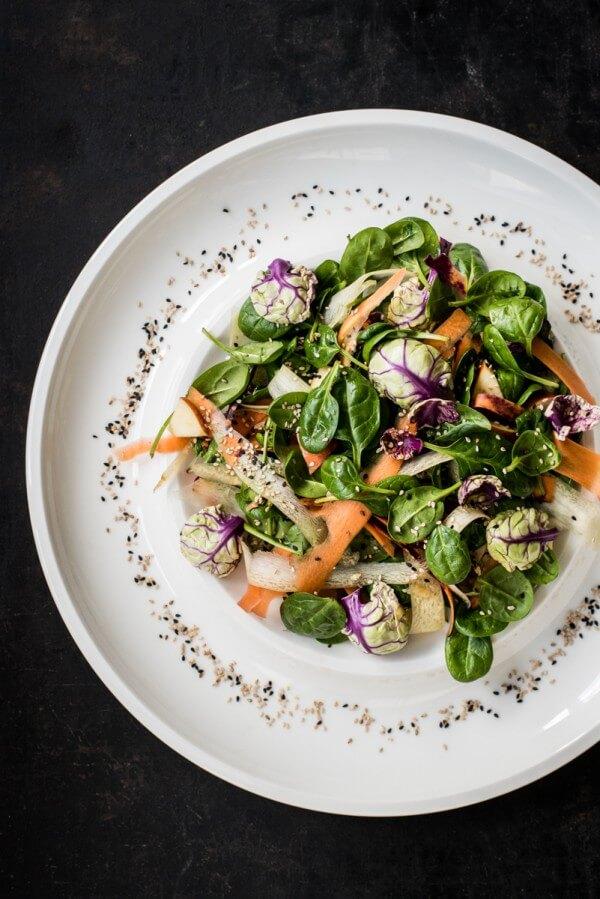Wintersalat aus Spinat, Rosenkohl und Karotten mit Sesam-Apfel-Dressing