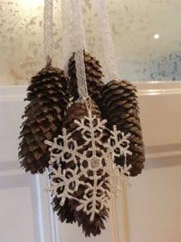 weihnachtliche Türdeko aus Tannenzapfen und Spitze