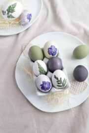 Natürlich gefärbte Ostereier mit echten Blüten verzieren.